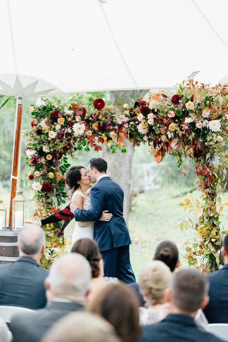 First Kiss Beneath a Chuppah Adorned with Fall Blooms and Leaves