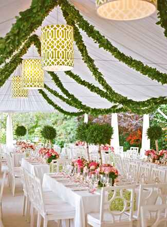 Tented wedding reception with green garland accents