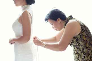 Mother of the bride helps bride button her wedding dress