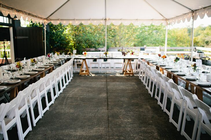 At the reception, a tent was set up outside that spread out the seating. Long wood tables were connected to each other, with simple table settings and centerpieces.