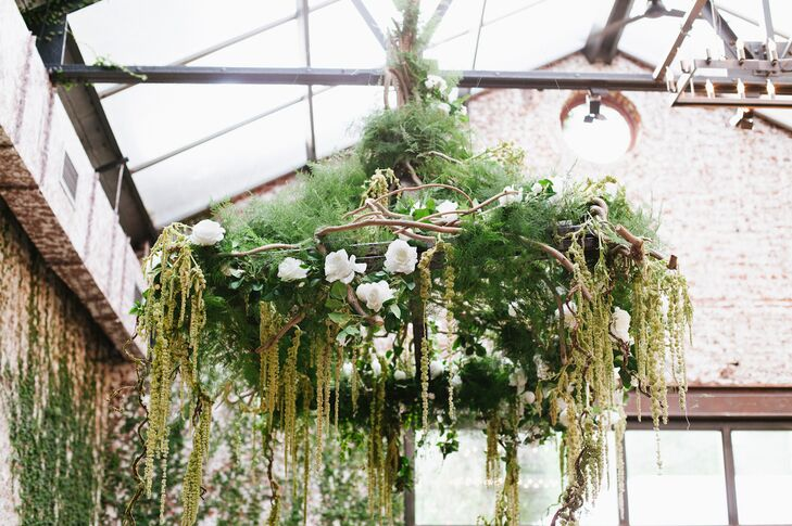 Because the walls of ceremony room were already covered in lush ivy, Sasha and Oli only added a hanging huppah made out of branches, moss and hanging amaranths.
