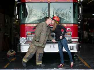 Firefighter engagement photo in front of fire truck
