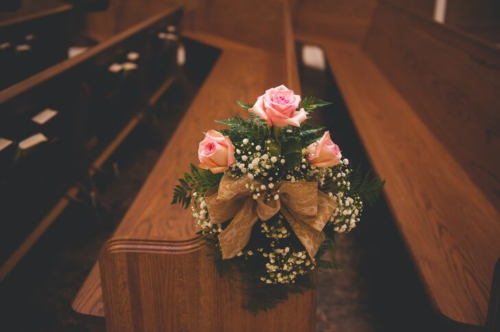 Pink roses accented with baby's breath were tied with gold ribbon and decorated ceremony pews at St. Paul the Apostle Church.