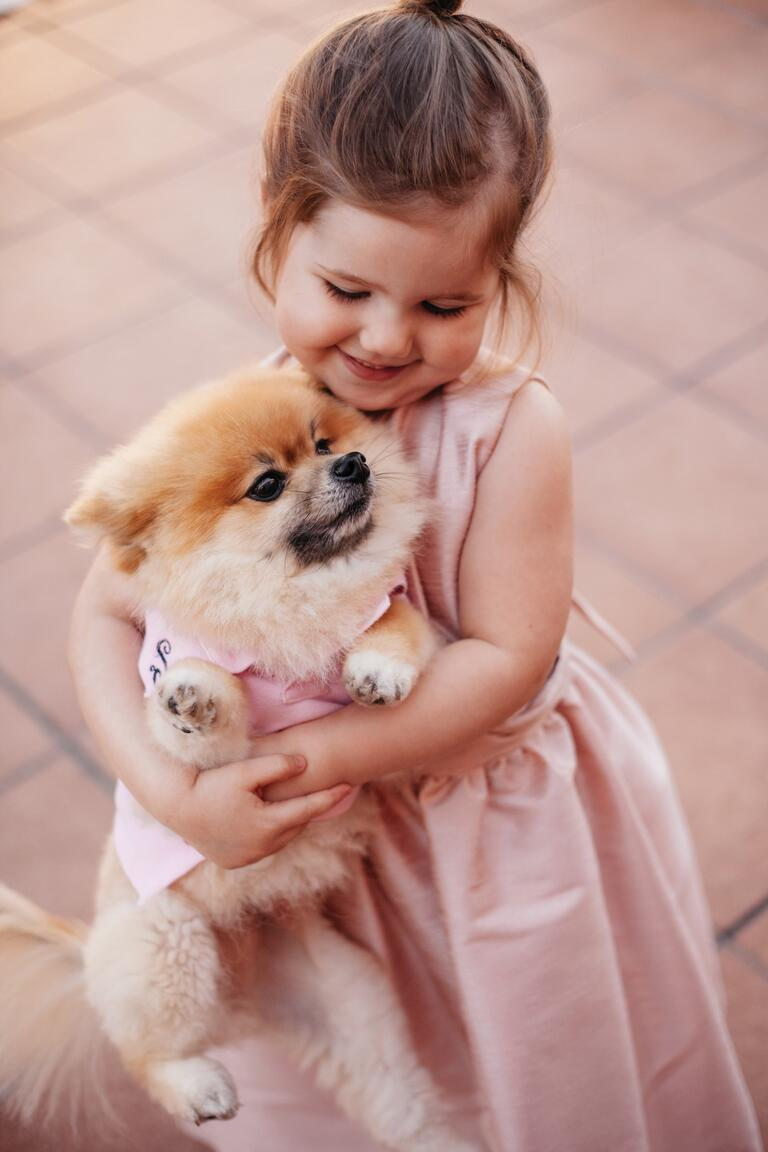 Flower girl hugging puppy