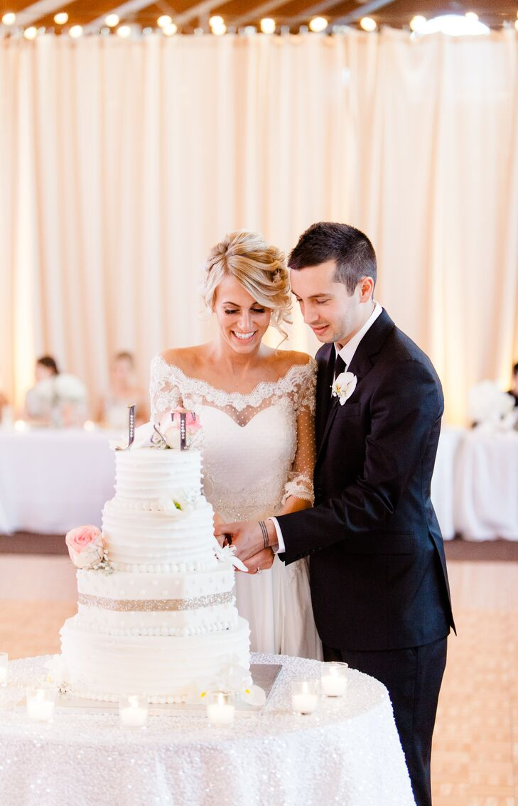 Jenna and Tyler cut their cake covered in white icing and filled with a variety of delicious flavors! Beaded icing rimmed the bottom of each layer, with one tier shaped like a hexagon that added a distinct look to the classic dessert.