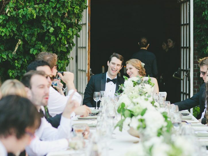 Bride and groom at long reception table