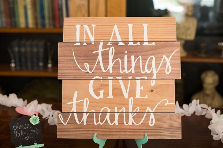 "Wedding signs made of wood panels decorated the day, giving the elegant occasion a bit of a rustic edge. This sign had white writing that read ""In all things give thanks,"" perched up by a mint green stand."