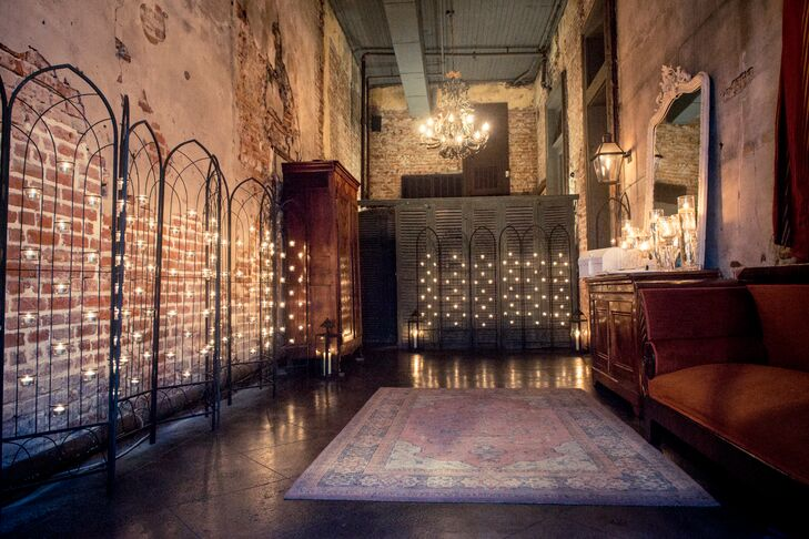 "Taking inspiration from their venue, Latrobe's on Royal in New Orleans, Louisiana, their entrance was lined with these chic iron arches covered with tiered tealight candles. Each one added a soft glow against the exposed bright walls and vintage decor. ""It looked amazing against the window and rustic mirrors,"" Kendra says."