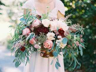 Overgrown bridal bouquet with red, pink and blush flowers