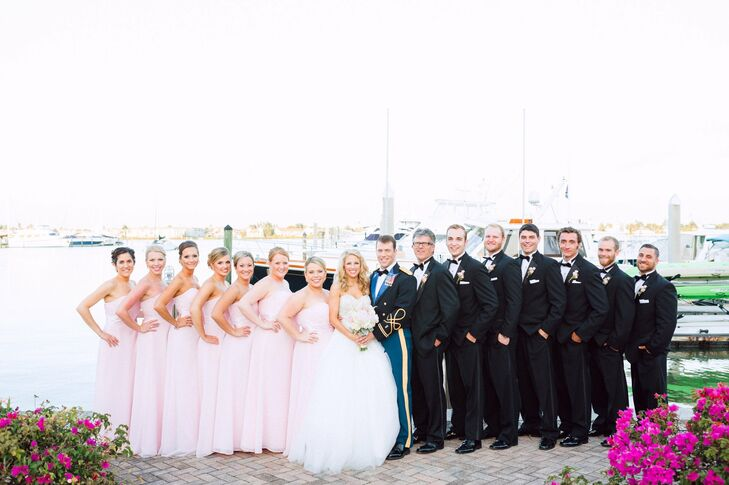 The groomsmen wore black suits with black bow ties, while the bridesmaids wore pastel pink floor-length gowns.