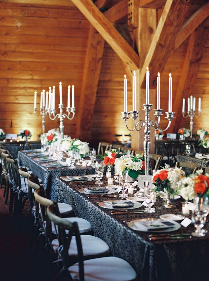 "The floral arrangements were modern and simple, in shades of white, silvery green, orange and yellow. ""We wanted to keep our flowers relatively low-key,"" Brett says. The candelabras added elegance to the tablescape."