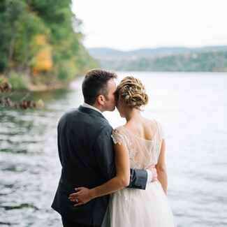 Newlyweds standing near water in West Virginia