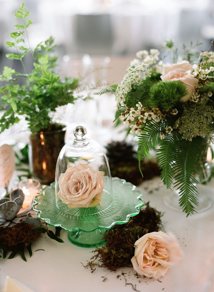 Single roses were displayed on green sea-glass cake stands under clear-glass terrariums. Green trick dianthus, wildflowers, ferns and moss added a rustic woodland feel.