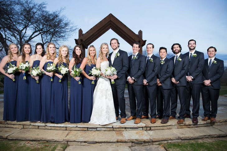 The couple decided on navy groomsmen suits to fit their less-formal style. They also got the groomsmen hand-stamped custom tie clips with their initials. The bridesmaids wore long navy dresses to be comfortable in the winter wind at the rural ranch.