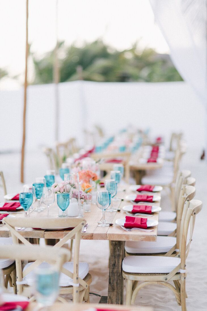Dining tables and chairs in light wood, set up on the sand, had turquoise glasses, pops of pink and coral flowers, which added to Danielle and Jason's rustic, casual reception vibe.