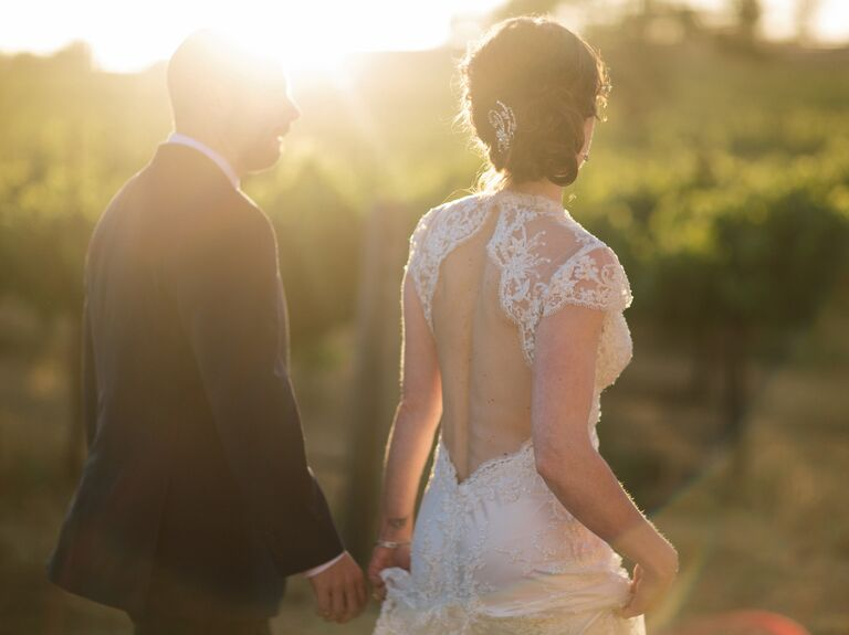 Bride with backless dress and groom in vineyard
