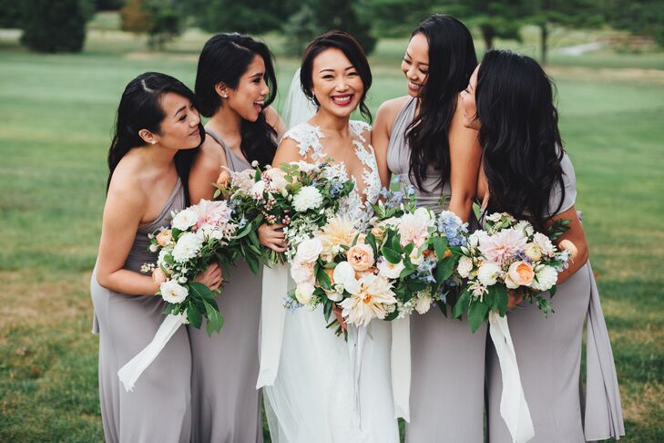 To keep things feeling cohesive while letting her bridesmaids show off some of their own personality, Yan had them wear convertible gowns from Lulu's in a soft, flowy lavender-gray fabric. The girls wore their hair down in loose, romantic waves and completed the look with simple stud earrings.