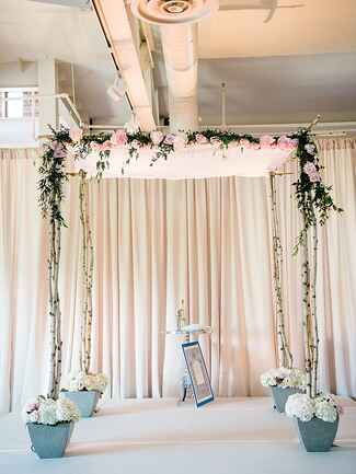 A birch huppah decorated with peonies and fresh foliage garlands