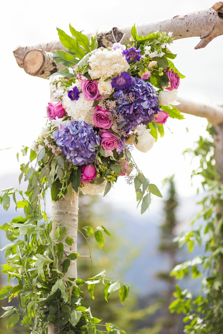 Purple And Pink Flower Arrangements On An Aspen Wedding Arch