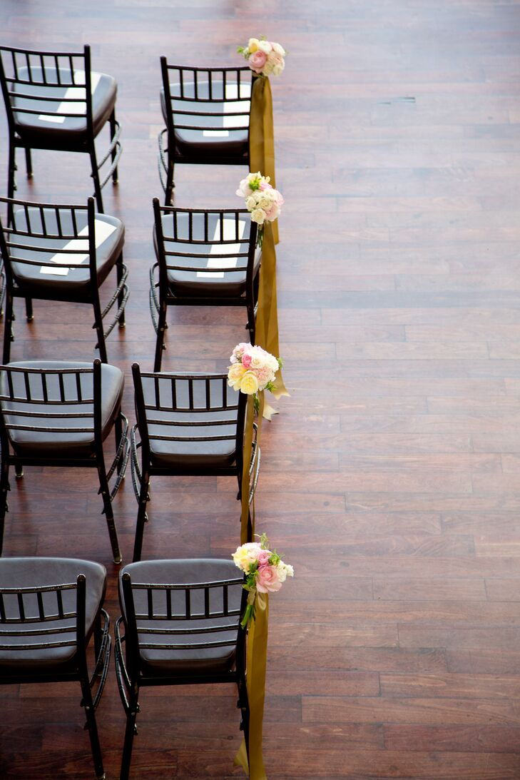 Wanting to keep the focus on the occasion at hand and The State Room's stunning city views, Alexandra and Dan kept the decor on the more understated side. They added only a few small bunches of pink and ivory roses and peonies to the aisle and two statement cherry blossom arrangements to frame the spot where they would exchange vows.