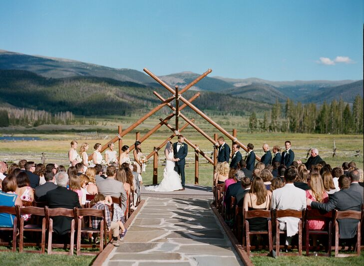 "Nicole and Alex's outdoor wedding ceremony was held beneath a rustic timber arch at Devil's Thumb Ranch. ""We went back and forth on how we wanted to decorate the ceremony site,"" says Nicole. ""We ultimately decided that we didn't need any decorations at all, the view of the mountains and the ranch is spectacular enough."""