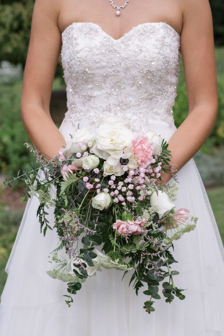 Kate carried a lush bouquet including white roses, pink carnations, white Queen Anne's lace and leafy greenery in her lush bouquet. Kate loved how the colors popped against the natural location.