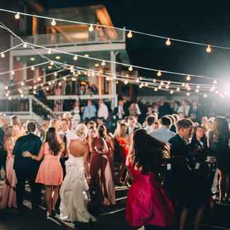 wedding guests dancing outside under bistro lights