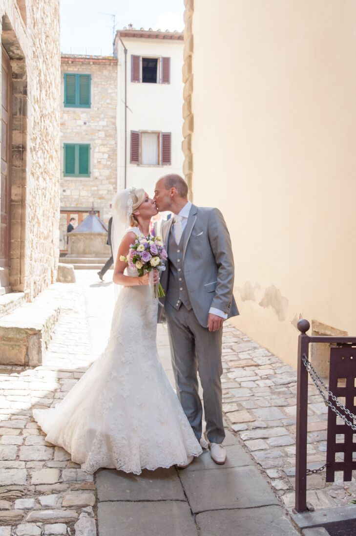The bride and the groom kissed in the streets of Tuscany. The bride wore a white wedding dress designed by Nicole Spose while the groom wore a gray tuxedo with a matching vest.