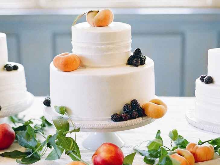 White wedding cake with apricots and blackberry garnishes