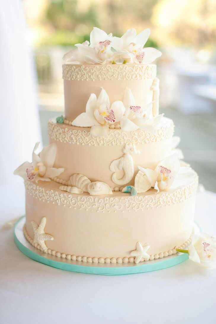 The bakers at Signe's Heaven Bound Bakery created this pretty beach-themed wedding cake. The cake was three tiers and frosted with sand-colored buttercream. Simple piped filigree accented each tier and fondant seashells and seahorses drove home the theme. To finish it off, they added fresh white cymbidium orchids and wrapped the base with turquoise ribbon.