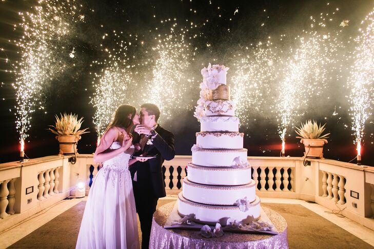 After indulging in a mouthwatering four-course meal, the newlyweds ushered their guests up onto Villa Miani's terrace. With the twinkling lights of Rome as their backdrop, the couple cut their colossal nine-layer cake as sparklers lit up the sky with sparkling light.