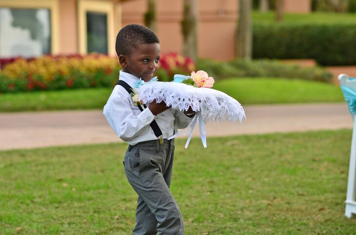 Ring bearer carrying ring pillow at an outdoor wedding ceremony