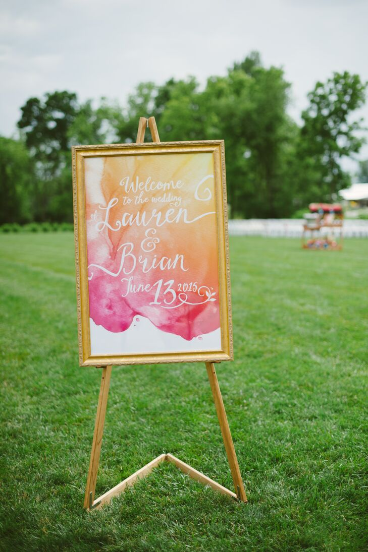 "A pink and orange watercolor pattern carried throughout the paper goods, including the beautiful gold-framed wedding sign that read ""Welcome to the wedding of Lauren and Brian"" with their wedding date at the bottom."