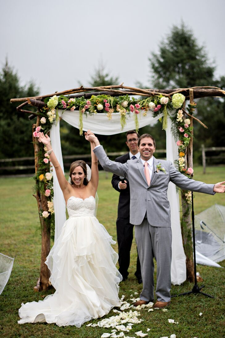 Noelle and Bobby's florist incorporated pink and green flowers from the bouquets into a rustic wedding arch. The second the ceremony ended, the rain cleared up and the sky broke out into a spectacular sunset that epitomized the magical moment of their nuptials.
