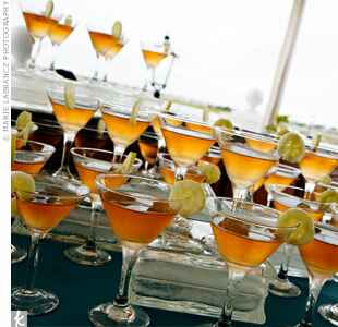 orange cocktails in a martini glass garnished with cucumber