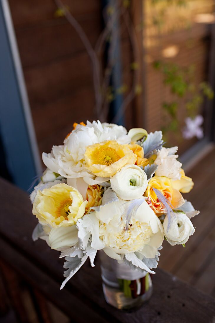 White and yellow roses, poppies, ranunculus, peonies and feathers made up the bridesmaids' lush bouquets.