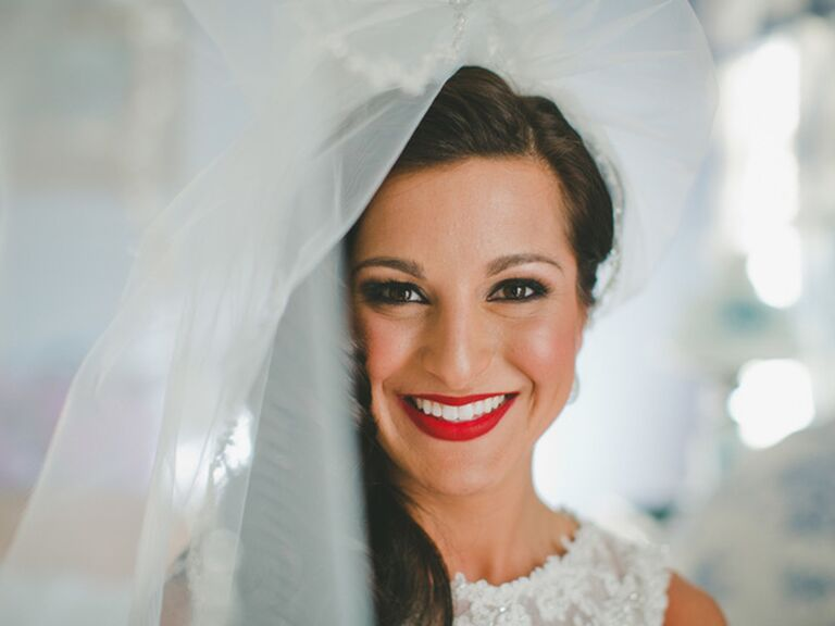 A bride with cherry red lips smiling while her veil blows away from her face