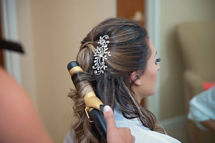 Mariel wore a glamorous sparkly crystal hair clip in her curled, half-down hairstyle. Her hair accessory perfectly complemented the David Tutera wedding dress, which she completed with a similar broach on a champagne belt.
