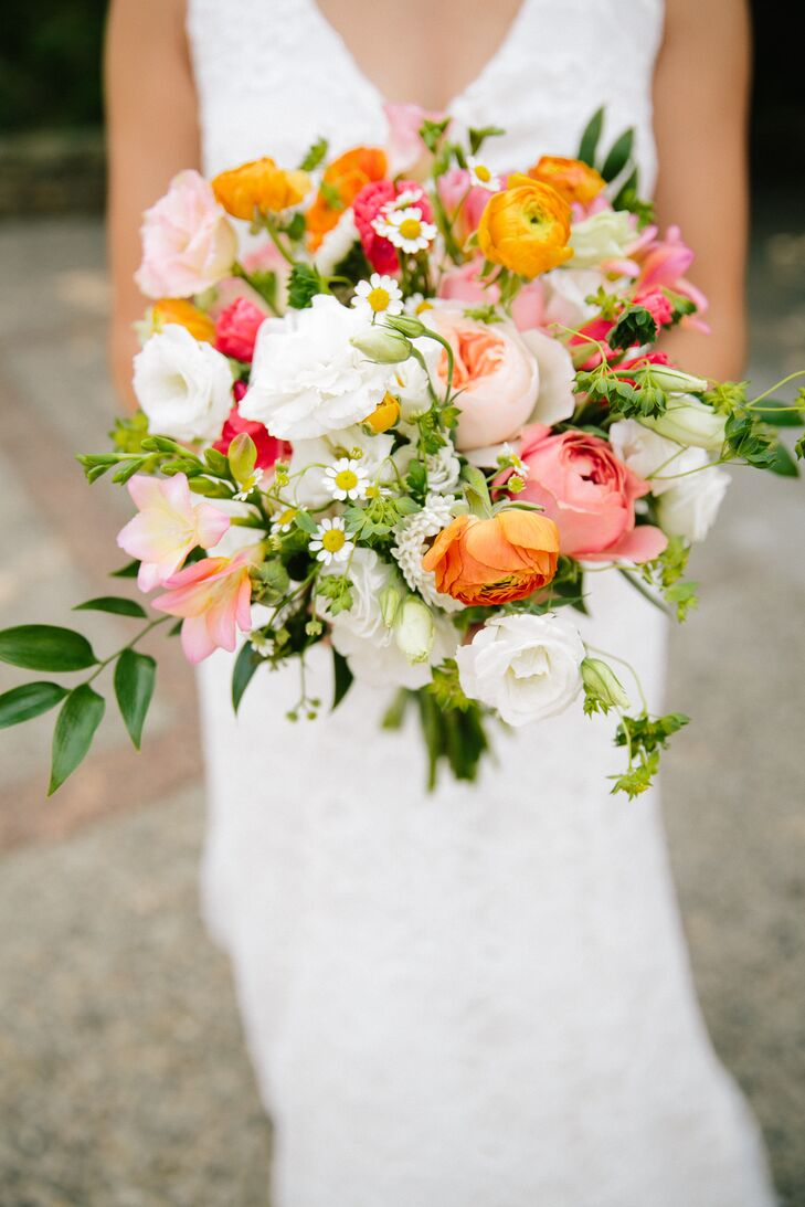 Katie carried orange ranunculus, white carnations, pink peonies, white daisies, white lisianthus and plenty of wildflowers in her bouquet. She loved the textured, overgrown look of the lush floral arrangement for her homespun, DIY wedding.