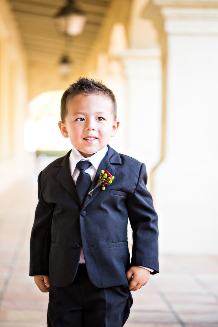 The ring bearer wore a charcoal gray suit with a matching tie over a white collared dress shirt. He had a red ranunculus boutonniere mixed with yellow hypericum berries pinned to his lapel.