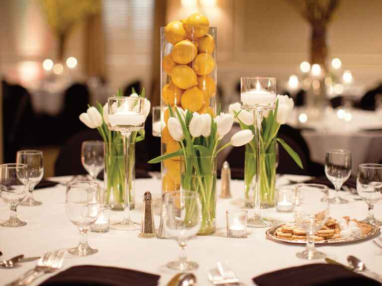 Hurricane full of lemons with tulip bouquets at wedding reception
