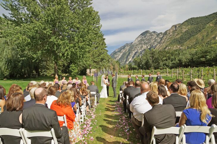 "Stephanie and Todd said ""I do"" with an unparalleled mountain view next to the vineyards at La Caille in Sandy, Utah. They had a flower-petal-lined aisle and a wedding arch dripping with wisteria. It doesn't get more romantic than that!"
