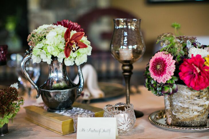 Vintage-inspired centerpieces, including eclectic fall-colored flowers in vintage teapots, wooden pots and scattered mercury-glass candles, continued the natural theme and created a warm atmosphere at the reception.