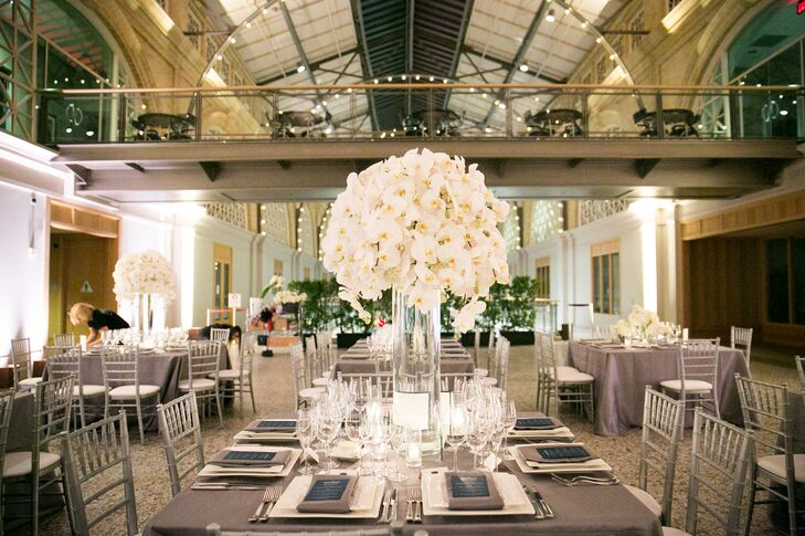 Guests sat at cleanly set dining tables covered with solid gray linens, with a navy blue menu card at each seat. The middle of tables had tall and low arrangements of white flowers—ranging from orchids to calla lilies and hydrangeas.