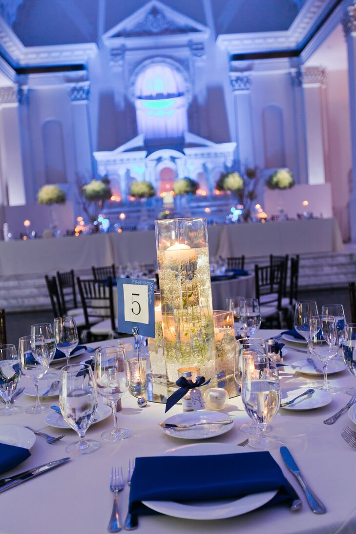 The Great Hall was transformed from the ceremony to the reception with round and long white dining tables set with sapphire blue napkins and white dinnerware. The tables were marked with blue and white numbers and decorated with glass cylinder vases filled with floating candles in water.