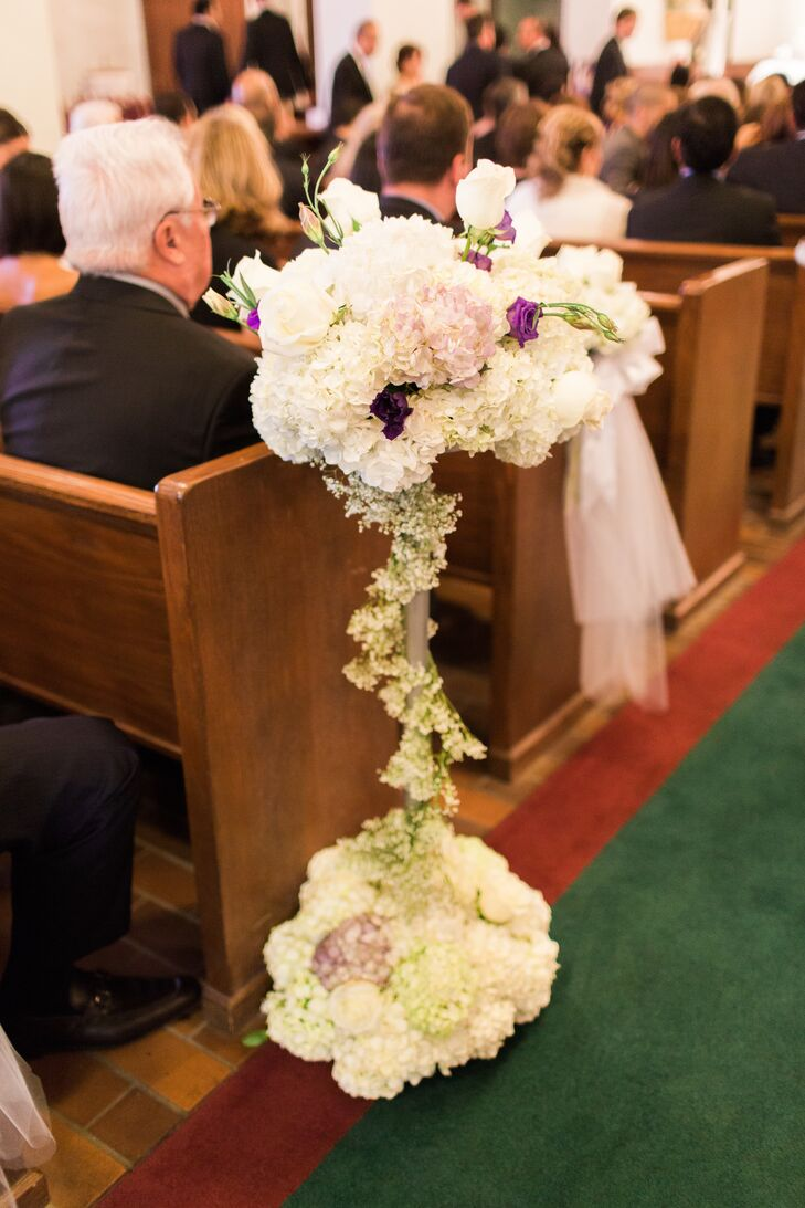 The couple lined their ceremony aisle with white tulle as well as tall, whimsical arrangements of white and green hydrangea, purple roses and white roses.