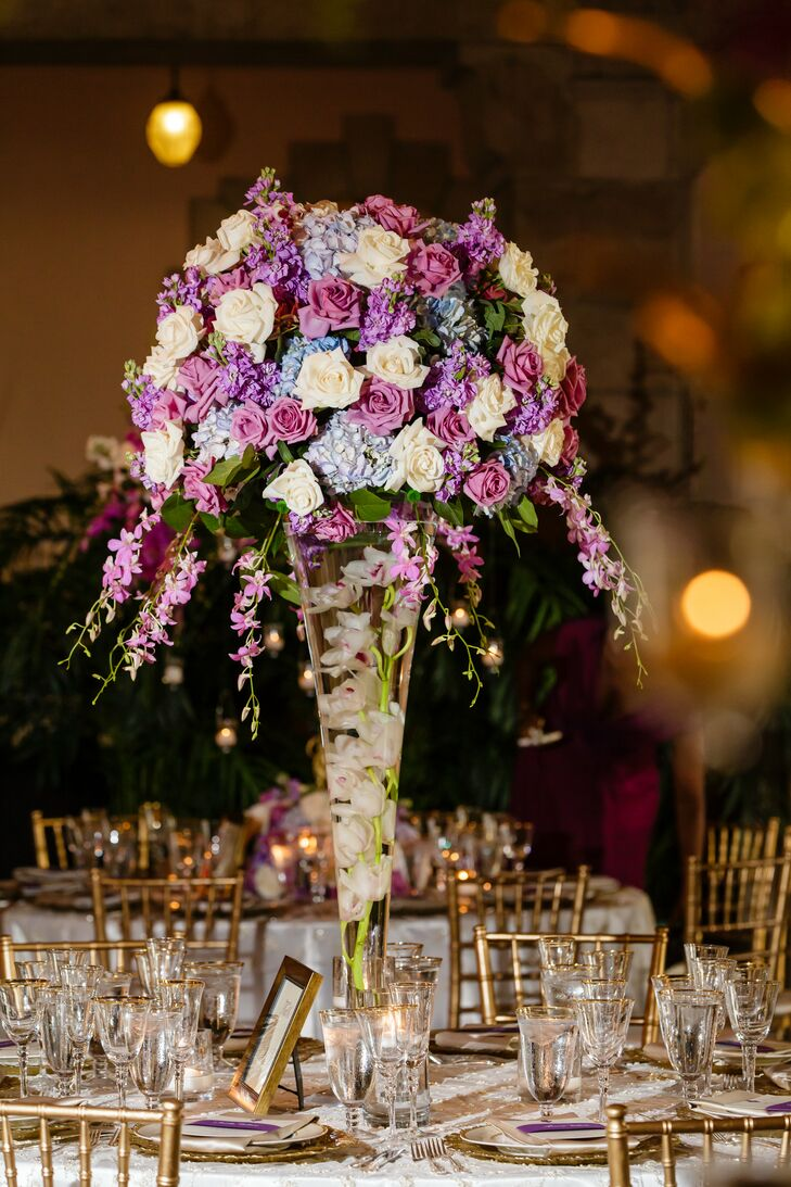 Each table was set with one of two centerpieces. Some included floating white cymbidium orchids in trumpet vases under a lush arrangement of purple roses, ivory roses, light blue hydrangeas and pink accents. Others had whimsical pink cymbidium orchids, roses and greenery along winding gold branches with hanging tea light candles.