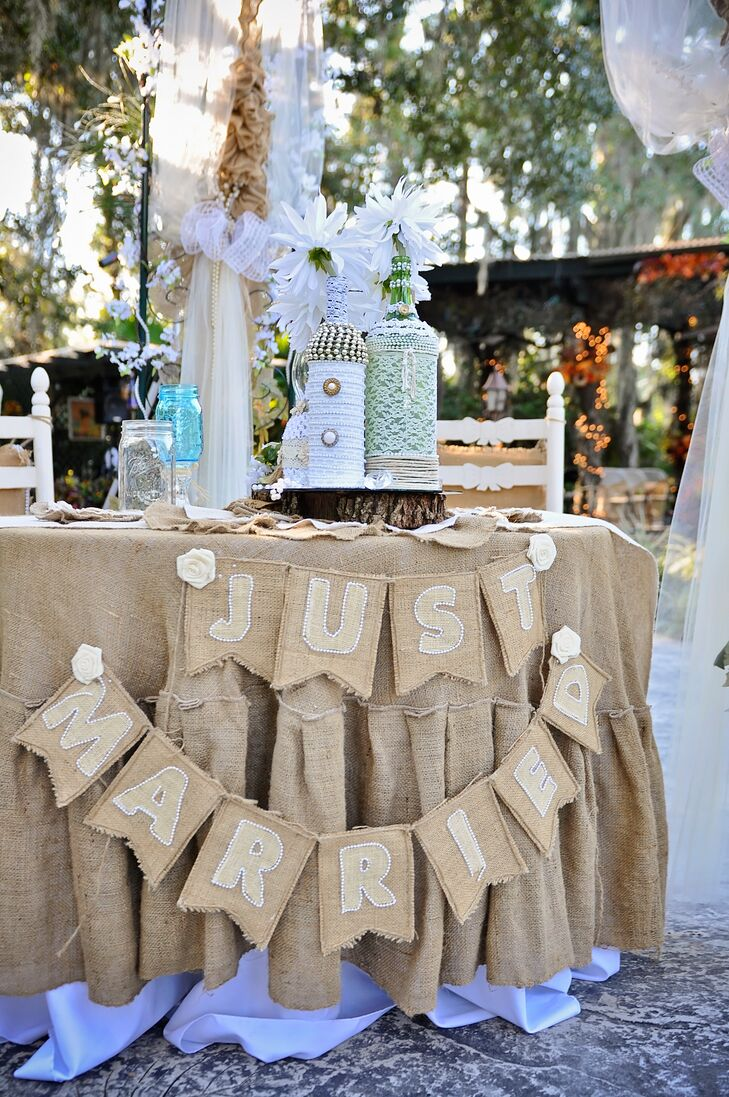 "Their sweetheart table was covered in burlap. Placed below an archway dripping in the fabric and tulle, their actual table was covered with a burlap linen and matching a burlap ""just married"" banner."