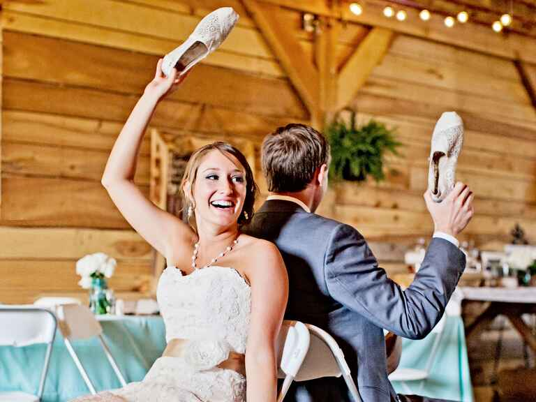 Bride and groom holding up a shoe at their wedding reception