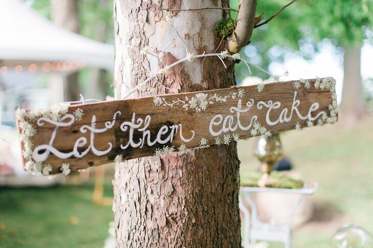 "As a nod to the Marie Antoinette-inspired motif, trees were hung with DIY wooden signs that read ""Let Them Eat Cake."""